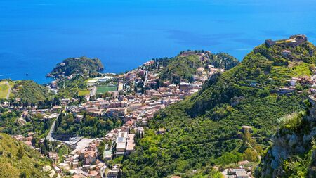 Aerial view of Taormina, on right is Castello Saraceno, in center is Ancient Greek theatre. Taormina located in Messina province on Sicily island in Italy.