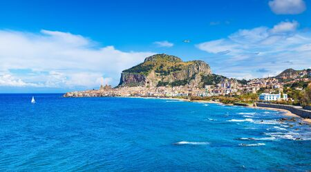 ong sandy beach and blue sea in Cefalu, town in Italian Metropolitan City of Palermo located on Tyrrhenian coast of Sicily, Italy. Cefalu is popular travel destination in Europe.