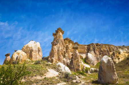 Rocks looks like mushrooms near Cavusin, Cappadocia, Turkey. Beautiful sunny day with blue sky and white clouds in Cappadocia.