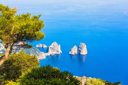 Aerial view of Capri Island and famous Faraglioni Rocks, Italy. Beautiful paradise landscape with azure sea in sunny day. Island of Capri is situated 5 km from mainland in Bay of Naples.