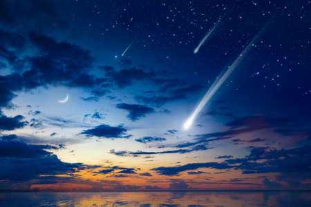 Amazing heavenly image with beautiful glowing sunset, comet and shooting stars, rising crescent moon and bright stars above sea. 免版税图像