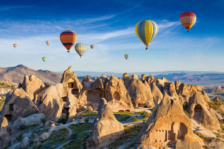 Sunrise view of unusual landscape in Cappadocia, Turkey. Colorful hot air balloons fly in blue sky over amazing rocky valley in Cappadocia.