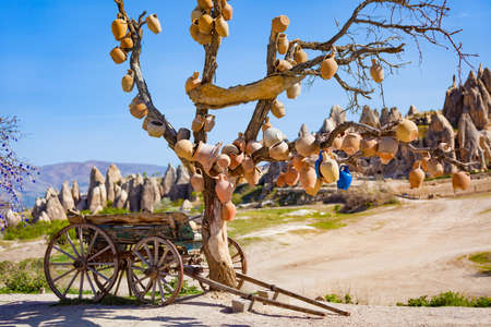 Goreme National Park, Cappadocia, Turkey. Old wooden cart stands under dead tree with clay pots hanging from its branches. Unusual landscape with conical rocks is in blurred background.