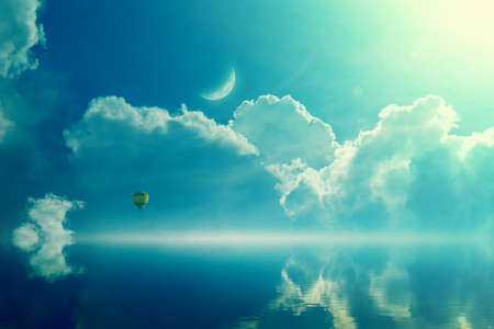 Amazing heavenly image - crescent and hot air balloon rising above serene sea, light from heaven.