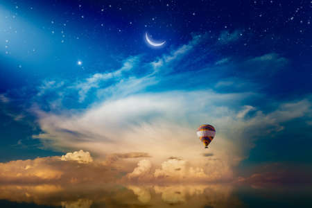 Amazing heavenly background - crescent and hot air balloon rising above serene sea in sunset glowing sky, light from heaven. 免版税图像