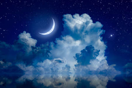Big crescent moon and clouds in night starry sky is reflected in calm sea. Silence, calmness and serenity. 免版税图像