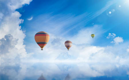 Amazing heavenly image - hot air balloons rising above serene sea, light from heaven, white clouds reflected in water.
