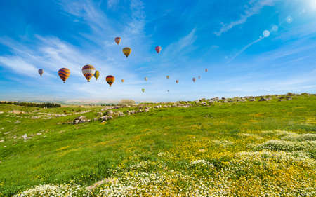 Daylight view of hot air balloons fly in blue sky over green hills near Denizli, Turkey.