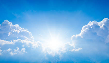 Beautiful religious image - bright light from heaven, light of hope and happyness from skies. Sun shines in blue sky above white clouds.