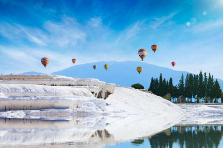 Amazing white travertine terrace formations, pool with clear hot water from thermal springs in Pamukkale, Denizli Province in southwestern Turkey. Hot air ballons fly above white Pamukkale. 免版税图像