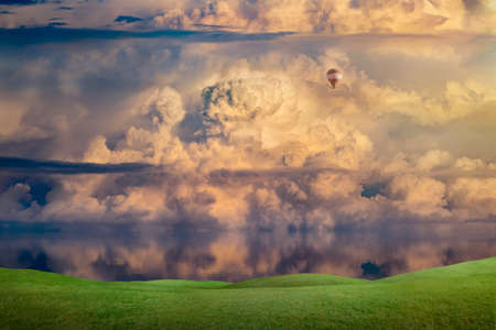 Lone hot air balloon flies high in sky with cumulonimbus clouds over calm sea. Weather forecast concept image.