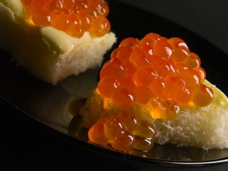 close-up of red caviar sandwiches on black saucer and black background. shallow dof.