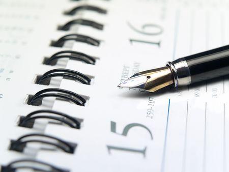 closeup of fountain ink pen over spiral calendar reminder. shallow dof photo