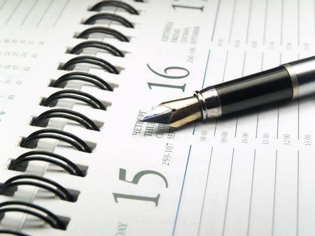 closeup of fountain ink pen over spiral calendar reminder. shallow dof