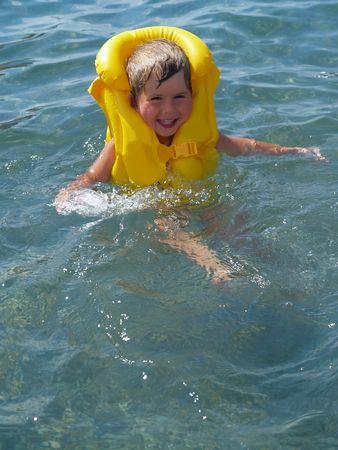 salvavidas: sonriente muchacho a salvar vidas chaqueta amarilla aprender a nadar