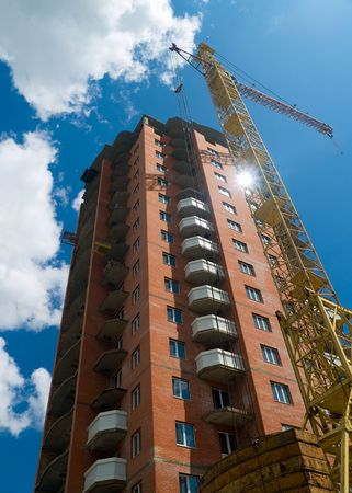 building construction, crane, blue summer sky with clouds Stock Photo