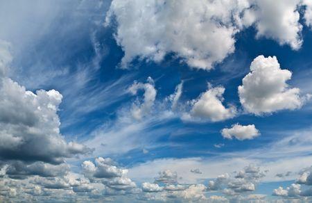 descriptive: blue summer sky with bright clouds. horizontal