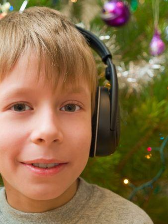 smiling boy in headphones portrait. christmas  tree background photo