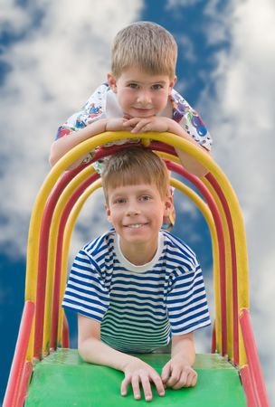 two caucasian boys playng on the slide over sky Stock Photo - 2993485