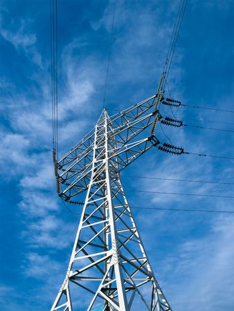 high-voltage transmission tower over blue sky with clouds Stock Photo