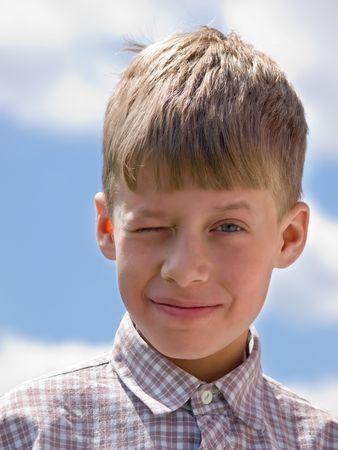 caucasian boy closeup portrait over blue sky photo