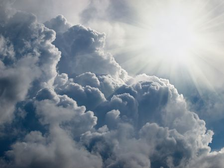 sun beams over blue sky with clouds
