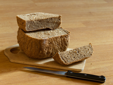 home made dark bread and knife on desk  shallow dof
