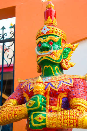 formidable: Colorful formidable statue at the entrance of a Buddhist temple with weapon in hand