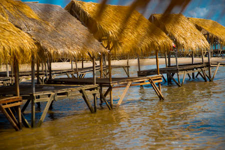 Island with houses made of straw near the river in Cambodia.
