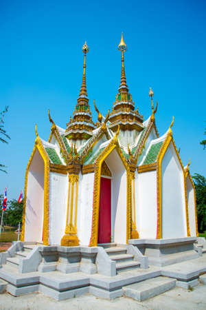 the gilding: Beautiful religious building is white with gilding on a blue sky . Ayutthaya Thailand.