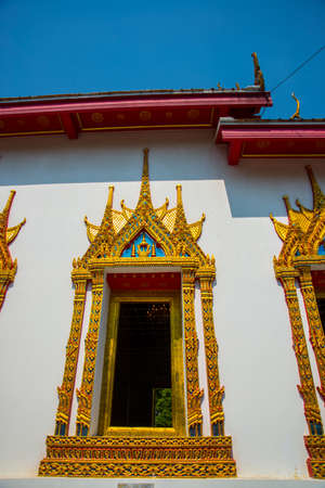 the gilding: Beautiful religious building is white with gilding on a blue sky . Ayutthaya. Thailand.