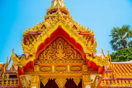 the gilding: A fragment of decoration on the roof.Beautiful religious building is white with gilding on a blue sky background. Ayutthaya. Thailand.