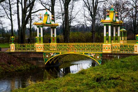 pool halls: Chinese bridge with yellow decoration. Autumn.Russia,the town of Pushkin, Tsarskoe Selo. Alexander park. Stock Photo