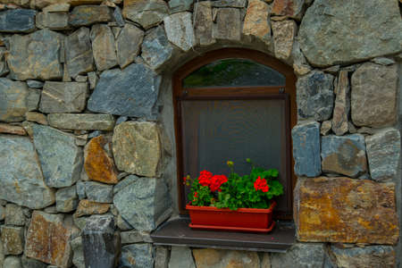 alan: The monastery of stone, an old Church in the mountains. Alan Svyato-Uspensky monastery, which is located in Fiagdon.Hidixys.A window on stone wall background.Red flowers in a pot. Stock Photo