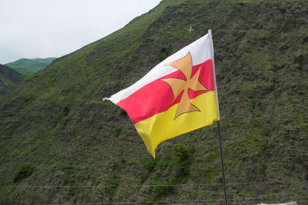 alan: Alan flag flutters in the wind.Color white, red with yellow cross in the middle.The Caucasus.Russia