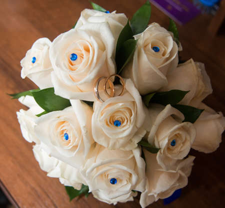 amorousness: Two beautiful wedding rings lie on a bouquet of white roses.
