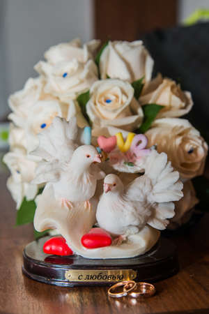 amorousness: Two beautiful wedding rings lie the table.Figurine doves.Love.Hearts.
