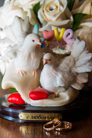 spousal: Two beautiful wedding rings lie the table.Figurine doves.Love.Hearts.