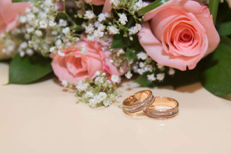amorousness: Two beautiful wedding rings lie the table.Beckett pink roses.