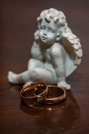 amorousness: Two beautiful wedding rings lie on the table.A small sculpture of a white angel. Stock Photo