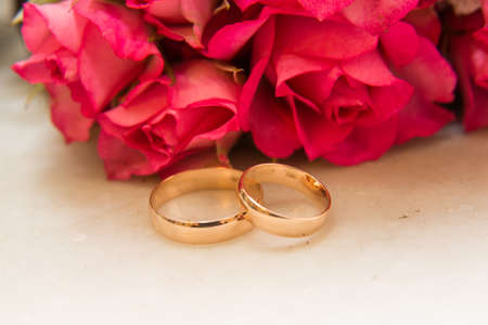 amorousness: Two beautiful wedding rings lie on the table in front of the bright red roses