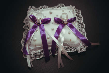 amorousness: Two beautiful wedding rings  lie on the pillow with a purple ribbon