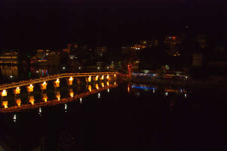 rajhastan: Beautiful view of the city. The bridge in lights. House, mountains on the horizon. Panorama city Udaipur, India