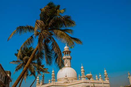ali: Fragment of a building on blue sky background. Palma. Mosque in middle of the sea in Mumbai. Haji Ali.