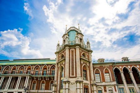 Tsaritsyno palace in Moscow, Russia. Brick historic building on the background of blue sky with white clouds in summer.