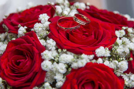Two beautiful engagement rings and Bridal bouquet of red roses.
