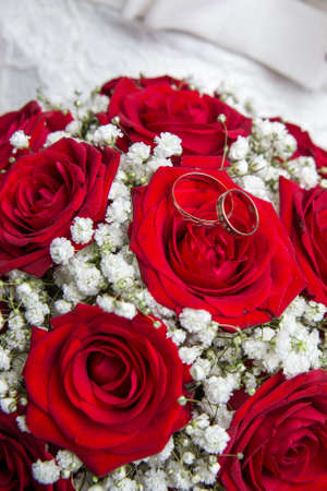 engagement rings: Two beautiful engagement rings and Bridal bouquet of red roses.
