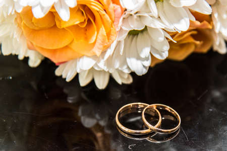 Two beautiful wedding rings and a wedding bouquet of orange roses and white colors. Stock Photo