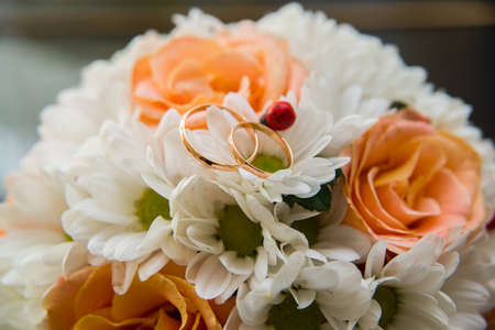 Two beautiful wedding rings lie on a wedding bouquet of orange roses and white colors. Ladybug.