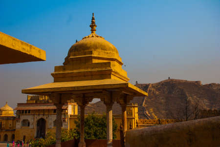 amber fort: Amber Fort illuminated by warm light of the rising sun and reflected in the lake. Famous Rajasthan landmark located nearby Jaipur city in north-western India. Stock Photo